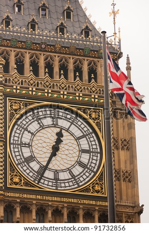 A close-up of the face of Big Ben, Westminster, with a Union Jack flag in the foreground