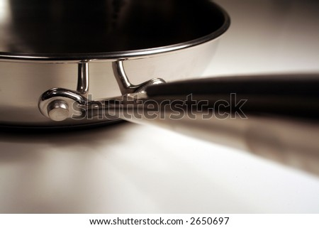 A close up of the handle of a stainless steel frying pan.