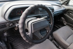 A close-up of the interior of a Russian driver's car seat and steering wheel made of plastic and a control panel with instruments and sensors in gray and black from cheap materials.