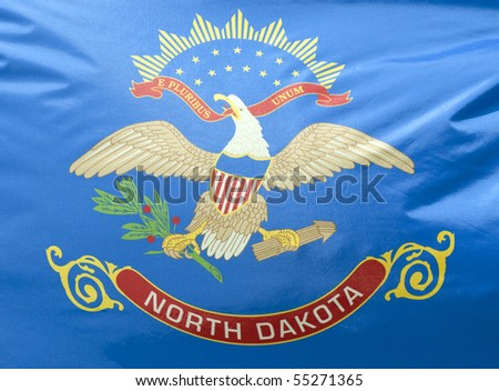 A close-up of the North Dakota state flag waving in the wind.