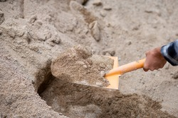 A close-up of the sand in the shovel, the hand of a construction worker shoveling the sand with a shovel. From sandpiles to mix cement on the construction site