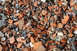 A close-up of the Thames foreshore in London, showing weathered red bricks, pieces of ceramic and glass, old bones and clay pipes, typically searched by mudlarkers