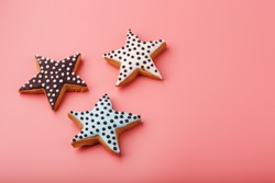 A close-up of three homemade glazed gingerbread cookies is made in the form of stars on a pink background. Handmade cookies.
