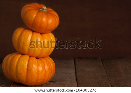 A Close Up of Three Small Pumpkins Stacked on Rustic Old Wooden Boards Against a Dark Brown Textured Background with Copy Space