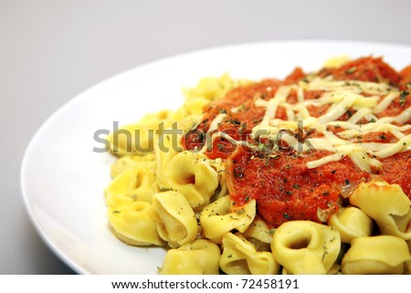 A close up of tortellini with tomato sauce and cheese served on a white plate