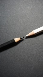 A close up of two colored pencils, one white one black pointing at each other coming in from opposite sides on a dark grey background.