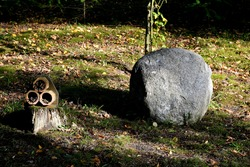 A close up on a large rock or boulder located next to a small hut made for insects and bugs seen in the middle of a public park next to a small tree and with leaves scattered everywhere in Poland