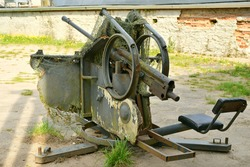 A close up on a masked and mesh covered artillery cannon from the Second World War rea standing next to abandoned barracks with its protective element and cloth covered seat visible seen in Poland