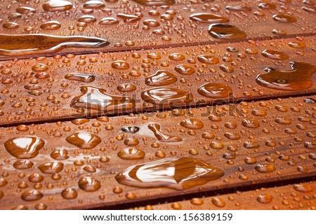 A close up on a recently sealed cottage deck just after the summer rain.  Water beads up in reflective pools as the sun begins to shine.