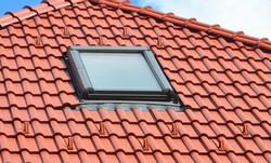 A close-up on a skylight installation on the ceramic tiled, clay tiled red rooftop.
