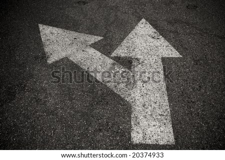 A close up on an arrow on pavement.