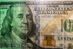 A close-up on banknote of the American dollars, The United States one-hundred-dollar bill ($100) with the image of Benjamin Franklin.