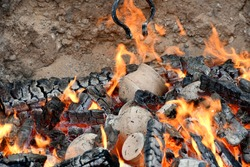A close up on clay pots and jugs being hardened in fire with flaming hot pieces of wood and coal scattered everywhere inside a sandy pit seen during a medieval themed fair in Poland