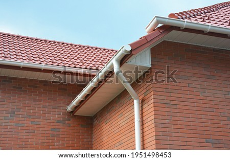 A close-up on plastic rain gutters, downspout, soffit and fascia with a box-end on the corner of a brick house as important parts of roofing system waterproofing and ventilation. Stock photo ©