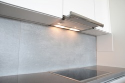 A close-up on under cabinet range hood, exhaust vent hood with lights working and modern electric stove, cooktop in gray and white kitchen design.