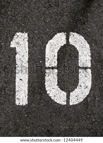 A close up on white stenciled number ten on black pavement.