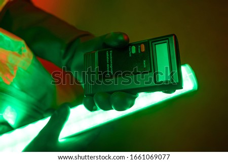 A close-up photo of a man in a protective radiation suit pointing to a Heger counter that he holds in his hands, illuminating it with uranium lamps. Radiation. Pollution. Danger. Dosimeter. Stock fotó ©