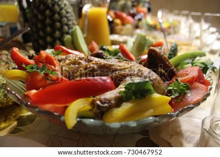 a close-up photo of a plate with a baked chicken and fresh vegetables on a festive table
