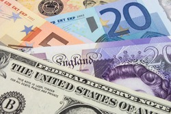 A close-up photograph of  United States and Euro and Sterling currency.
