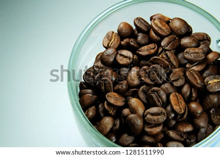 A close-up picture of a high quality roasted arabica coffee bean in a cup.