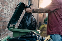 A close up picture of a young male hand throwing rubbish to the bin at the street. The black rubbish bin is for organic green waste collection. The bin lid is open. Copy space. Concept: Ecology