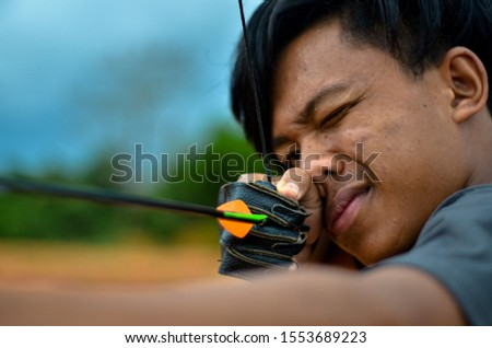 A close up picture of archer hold his bow to aim at the target #1553689223