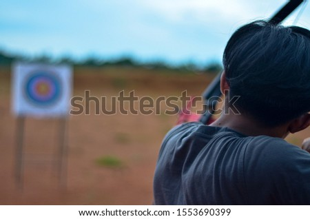 A close up picture of archer hold his bow to aim at the target #1553690399
