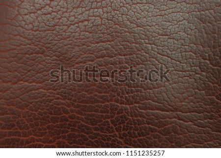 A close up picture of brown bison leather for a background texture. It is dark brown and shows the natural design of the animal skin and material.