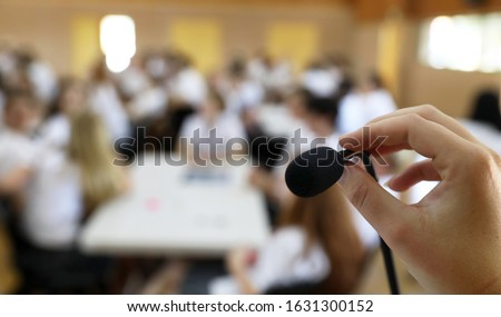 A close up point of view image of a hand  in focus holding  or adjusting a microphone while public speaking in front of a deliberately blurred audience in a hall or class room. Announcement idea