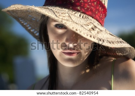 A close up portrait of a beautiful twenty something young woman in a sun hat with one eye showing.