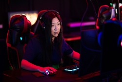 A close-up portrait of a gamer girl wearing headphones in a computer club while playing a game