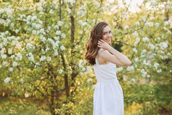 A close-up portrait of a happy pretty gentle smiling young woman with a hairstyle in a white cotton dress having fun walking alone enjoying the smell of blooming flowers in a summer green outdoor park