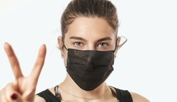 A close-up portrait of a pretty female wearing a surgical mask isolated on a white background