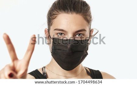 A close-up portrait of a pretty female wearing a surgical mask isolated on a white background Photo stock ©