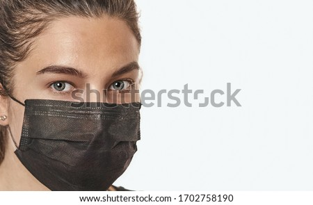 A close-up portrait of a pretty female with stethoscope wearing a surgical mask isolated on a white background. Stockfoto ©