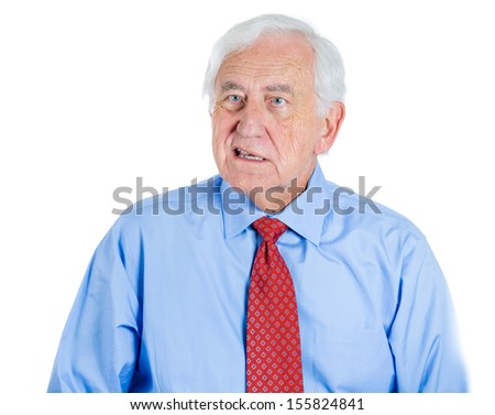 A close-up portrait of a senior unhappy executive, elderly man, grandfather with a very skeptical attitude, isolated on a white background . Human personalities and emotions, conflict resolution.