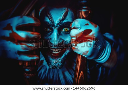 A close up portrait of a smiling clown from a horror film behind the railings. Halloween, carnival.
