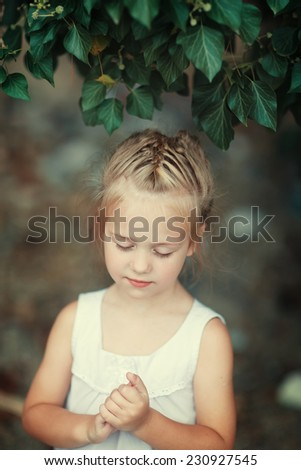 A close up portrait of a sweet smiling little girl in a white dress dreaming about something