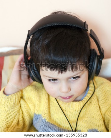 A close up portrait of a toddler boy listening to a music with headphones.