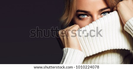 A close-up portrait of a woman. A beautiful young girl with blue eyes covers her mouth with a collar of white sweaters.fashion, beauty, makeup, cosmetics, beauty salon, style, personal care, posture.