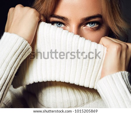 A close-up portrait of a woman. A beautiful young girl with blue eyes covers her mouth with a collar of white sweaters. #1015205869
