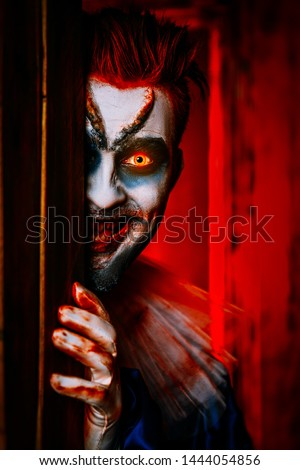 A close up portrait of an angry clown from a horror film hiding behind a door. Halloween, carnival.