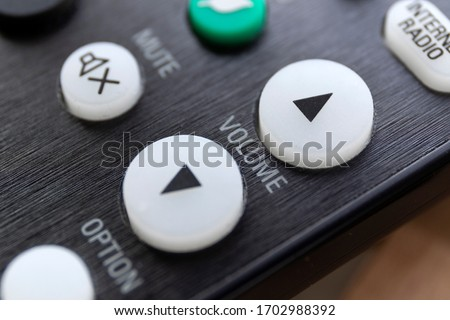 A close up portrait of the volume up and down buttons on a radio, television or surround sound system, used to alter the sound level. In the background the mute button is visible but blurred.  Foto stock ©