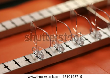 A close-up row of plastic lenses being manufactured. Can be used for plastics, optics, manufacturing and technology.