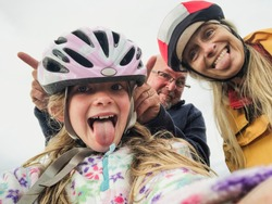 A close-up selfie of a happy family with one child, they are on an outdoor bikeride and pulling silly faces.