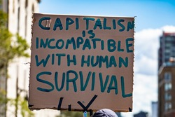 A close up shot of a cardboard sign saying capitalism is incompatible with human survival, as environmental activists stage a rally on a city street