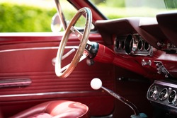 A close up shot of a fancy shiny inside of a red automobile