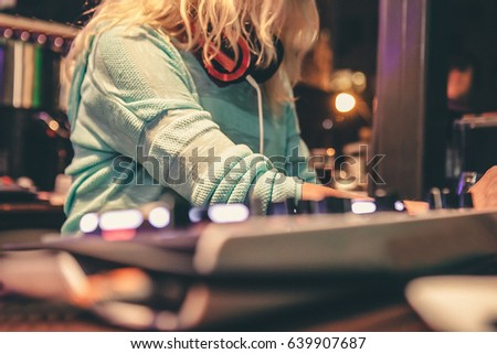 A close up shot of a female music deejay playing a set