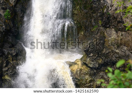 a close up shot of a large waterfall pool surrounded by rocky cliffs. Sort of a tropical feel with some green foliage present and hints of yellow hues forming on the stone as the powerful falls gush.