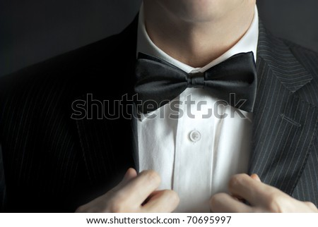 A close-up shot of a man straightening his tux.